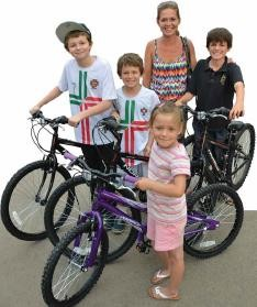 Family members proudly display their Mike's Bikes, received with helmets and locks.